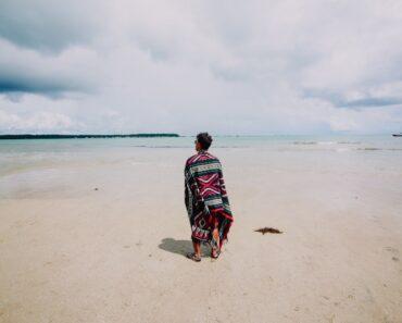 Momak stoji na plaži prekriven peškirom preko ramena i gleda u more