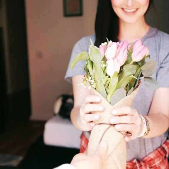 Devojka u rukama drži buket cveća