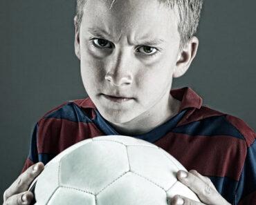 Dečak koji drži fudbalsku loptu u rukama