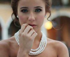 Devojka nosi bisernu ogrlicu