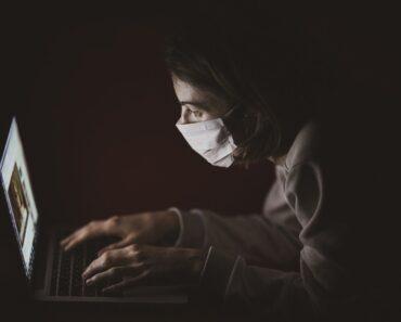 Čovek koji radi sa maskom u mraku na laptopu